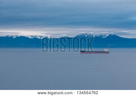 A freighter on a calm sea at dawn with snow capped mountains in the background