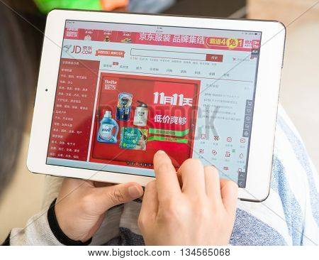 ZhongshanChina-November 11 2015: young woman shopping through ipad on jd on Chinese online shopping day on November 11. Nov 11 is the shopping day in China and many online shops sale things in half price starts from Nov 1 until Nov 11.