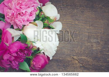 Peony background. Fuchsia, pink and white peonies on wooden table with place for text. Spring flower peon. Happy Mothers Day. Mother's Day greetings card. Mothers Day gift. Copy space. Toned image.