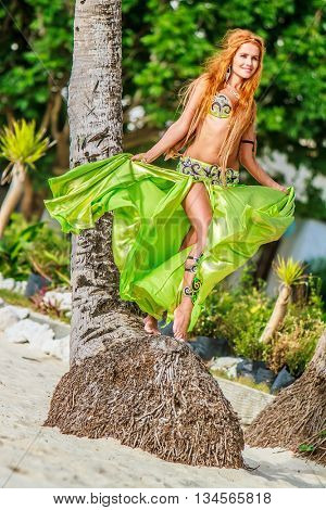 young beautful woman in awesome green dress for belly dance on tropical tree background, summer vacation on paradise island