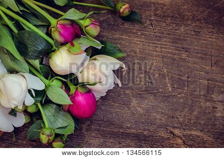 Peony background. Fuchsia, pink and white peonies on wooden table with place for text. Spring flowers peonies. Happy Mothers Day. Mother's Day greetings card. Mothers Day gift. Copy space.