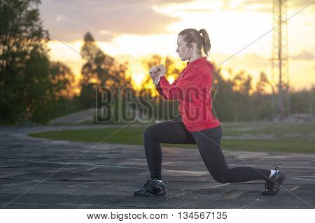 Young fit woman doing squats (frontal lunges) outdoors. Fitness workout sport outdoors concept.
