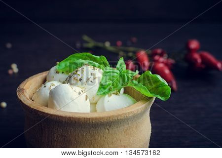 Fresh mini Mozzarella with basil in wooden plate on dark background with chili pepper. Portion of small Mozzarella Cheese. Mozzarella baby in plate. Selective focus.