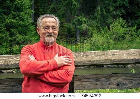 Portrait of a handsome senior man in bright sweater near the river and the forest. Looking at the camera. Smiling happy senior man with gray hair and beard. Outdoors. Horizontal image.