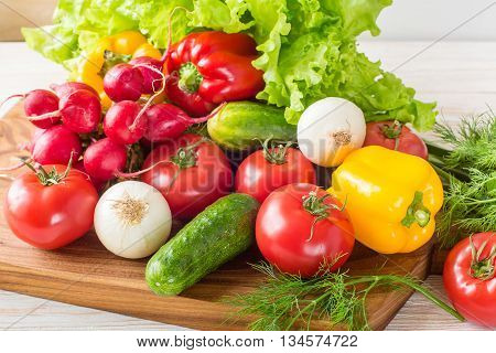 Close up of mixed colorful raw vegetables on wooden chopping board. Bright and fresh vegetables
