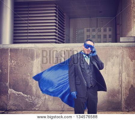 A business man is dressed up as a super hero using a phone in the city for a unique humorous or communication concept.