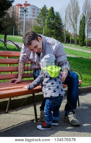Baby learning to stand with father support near the bench in spring park. Stylish boy in jeans and sneakers. Toddler and father have fun outside. Father's Day. Happy Fathers Day. Father and baby.