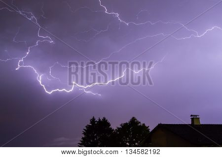 Lightnings over a house and a tree in the night with blue sky