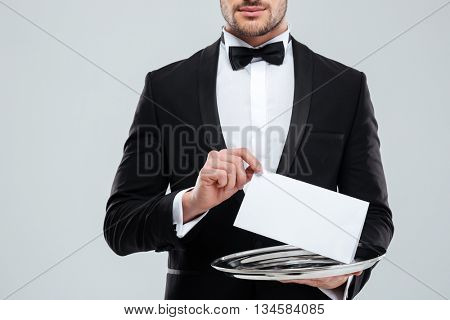 Closeup of waiter in tuxedo with bowtie holding blank card on tray