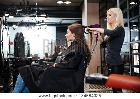 Stylist drying hair of a female client at the beauty hair salon poster