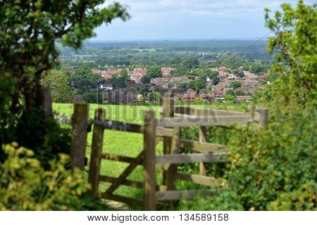 Gate or style overlooking typical English country village Sussex