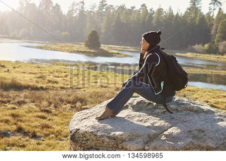 Young woman sits on a rock in countryside admiring the view