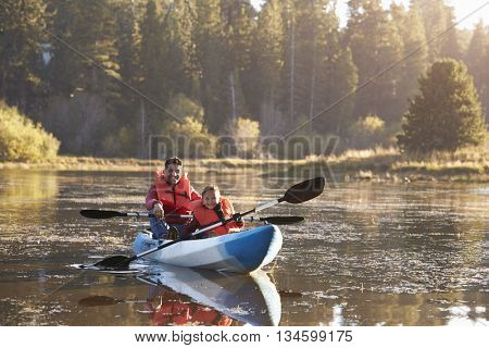 Father and son kayaking on rural lake, front view
