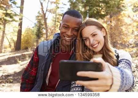 Smiling mixed race couple take a selfie in a forest