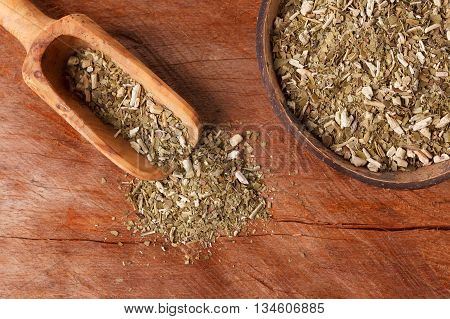 Mate With Wooden Scoop On Wooden Background