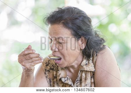 Portrait of beautiful senior woman eating her lunch/dinner at the table of home