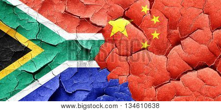 South africa flag with China flag on a grunge cracked wall