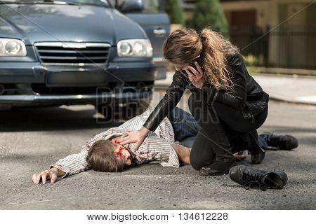 Image of woman calling ambulance for injured man