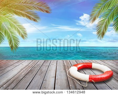 Wood pier with ocean and palm trees in background