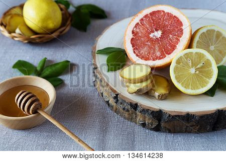 Grapefruit lemons and ginger on a wooden stand with a plate of honey