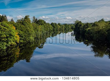 Trees reflected in river in landscape of the Tweed valley in Scotland