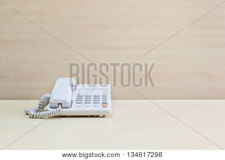 Closeup white phone office phone on blurred wooden desk and wall textured background in the meeting room under window light