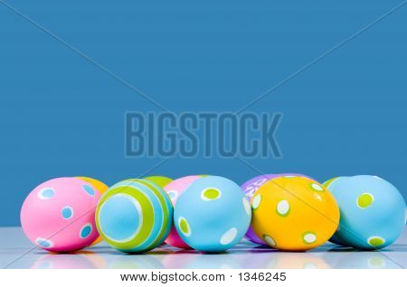 Brightly Colored Easter Eggs On Blue Background With Reflection