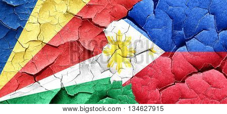seychelles flag with Philippines flag on a grunge cracked wall