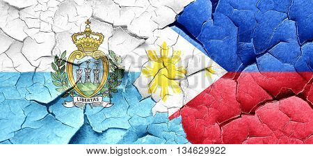 san marino flag with Philippines flag on a grunge cracked wall
