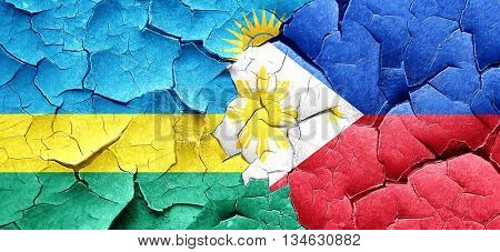 Rwanda flag with Philippines flag on a grunge cracked wall