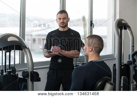 Personal Trainer Takes Notes While Man Exercising Legs