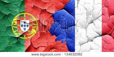 Portugal flag with France flag on a grunge cracked wall