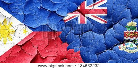 Philippines flag with Cayman islands flag on a grunge cracked wa