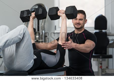 Personal Trainer Helping Man On Chest Exercise