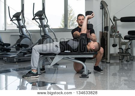 Gym Coach Helping Man On Chest Exercise