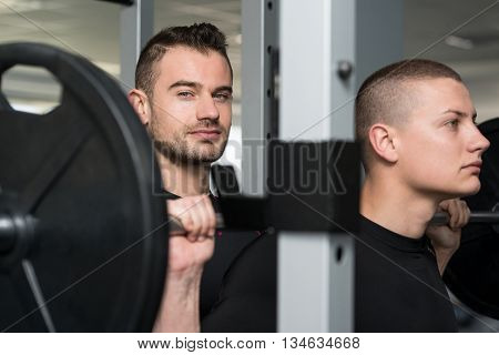 Man With Personal Trainer At Barbell Squat