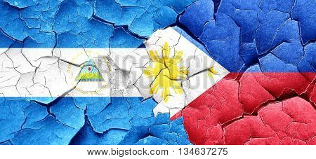 nicaragua flag with Philippines flag on a grunge cracked wall