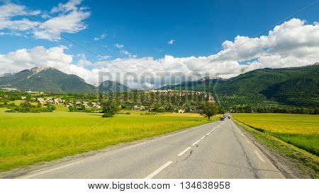 Paved Two Lane Road Crossing Mountains And Forest In Scenic Alpine Landscape And Moody Sky. Panorami