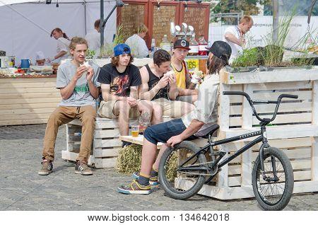 KHARKOV UKRAINE - JUNE 12 2016: A group of teenagers eating junk food in a street food area