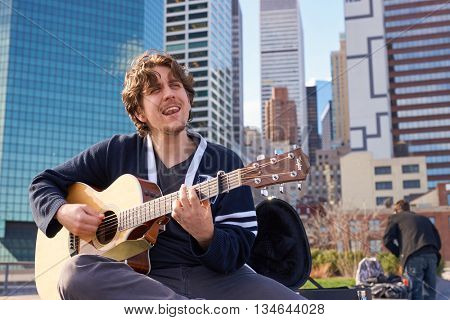 NEW YORK - MARCH 17, 2016: man sing song at Pier 15 at daytime. Pier 15 is located east of South Street and FDR Drive in Lower Manhattan, New York City.