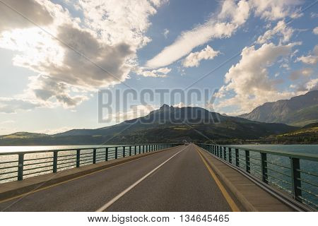 Paved Two Lane Road On Bridge Crossing Lake In Scenic Landscape And Moody Sky. Panoramic View From C
