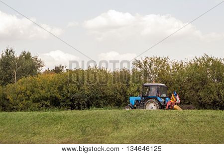 Tractor machine with grass cutter mowing lawn
