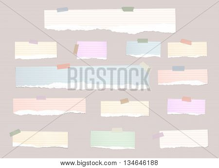 Torn colorful note paper pieces are stuck with sticky tapes on pink background.