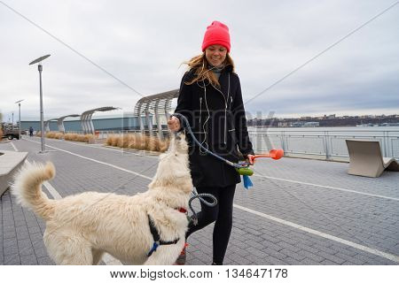 NEW YORK - CIRCA MARCH, 2016: outdoor lifestyle portrait of young woman with dog in New York. The City of New York is the most populous city in the United States