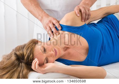Close-up Of Person Giving Massage To Mature Woman In Spa