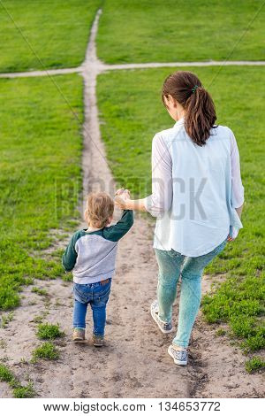 mom with a toddler is on treck. Mum with the child climbs up the hill. Little boy with his mother walking along the road on the hill in the parkin the summer.