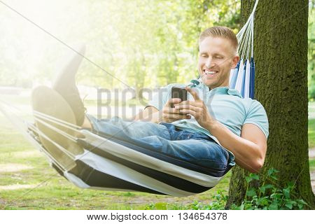 Young Happy Man Using Mobile Phone While Relaxing In Hammock At Garden