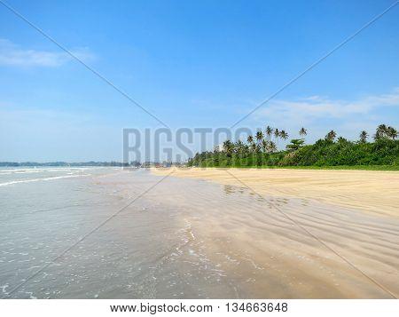 Empty tropical beach with sand and palms, Weligama, Sri Lanka