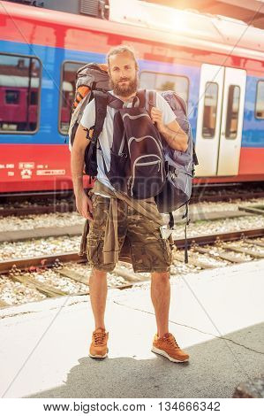 Handsome tourist traveler standing with huge luggage at the railway station near the tracks