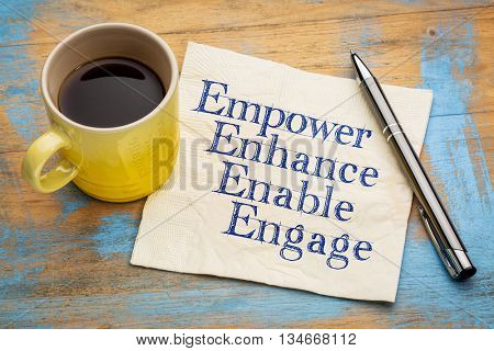 motivational leadership, coaching or business concept - empower, enhance, enable and engage  words on a napkin with a cup of coffee